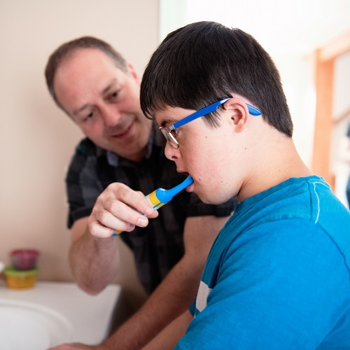 Father helping her son of 12 years old with Down Syndrome in daily lives brushing her teeth. He take care of her beautiful son. The little boy wear eyeglasses. Photo was taken in Quebec Canada.
